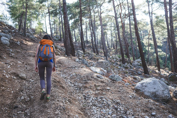A girl with a backpack goes along a mountain trail.