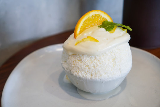 Yuzu Bingsu. A bowl of milk shaved ice topped with yuzu cream flavour and yuzu sliced on white plate at dessert cafe.
