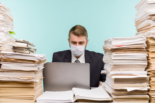 A male accountant or company manager works in an office in a pandemic in view of the accumulated paper work. A protective medical mask is on the face. On the desktop are large stacks of documents.