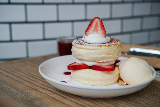 Strawberry soufflé pancake. Fluffy pancake topped with fresh cream and strawberry sliced, served with crumble cookie and vanilla ice cream.
