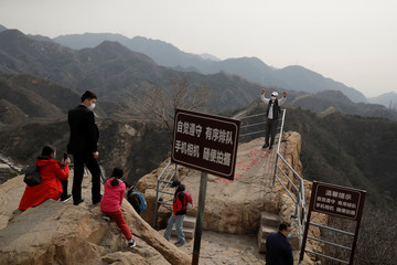 A man wearing a protective mask poses for a picture at the Great Wall in Badaling in Beijing