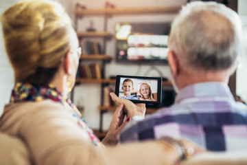 Senior couple making video call on digital tablet with their grandchildren.Quarantine. Health concept. Wall mural
