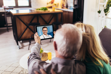 Senior couple at home holding digital tablet during video call with family doctor