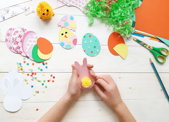 The child makes crafts with his own hands for the Easter. Colorful handmade from multi-colored paper. Scissors, cardboard, eggs, chicken, rabbit. Art creativity on a wooden table. Top view, copy space
