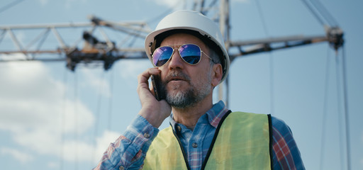 Engineer coordinating on phone on construction site