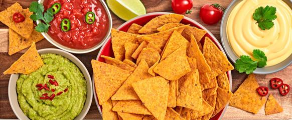 Nachos Mexican corn chips with guacamole, salsa, cheese dip sauce. Vegan nachos snack isolated on wooden board, top view. Tortilla nacho crisps closeup.