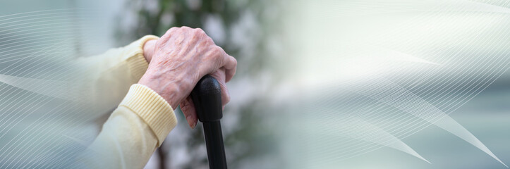 Old woman hands holding a cane; panoramic banner