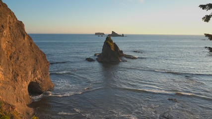 sunset shot of the hole in wall rock formation at rialto beach