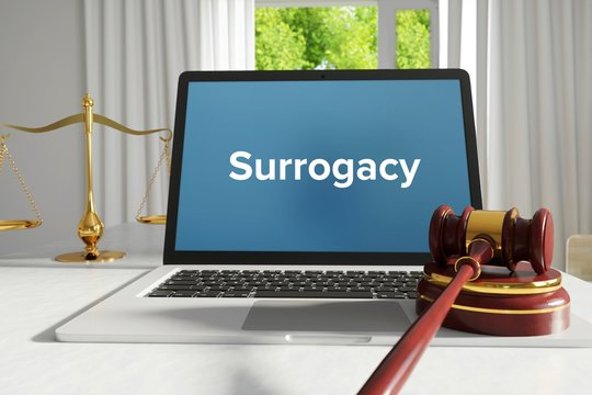 Surrogacy – Law, Judgment, Web. Laptop in the office with term on the screen. Hammer, Libra, Lawyer.