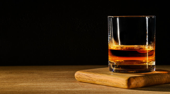Glass with whiskey on wooden table and black background. Copy space.