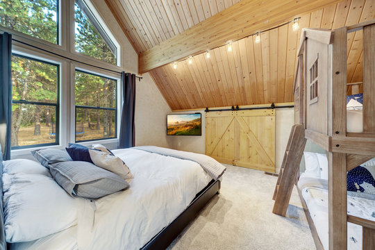 Amazing bedroom design with hige vaulted wooden ceiling, large windows, modern chandelier, TV, king size bed and cozy bedding,  Barn style railing doors to the closet.