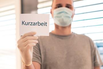 Mann mit Mundschutz und Einweghandschuhen  hält Zettel mit dem Wort Kurzarbeit - Konzeptbild Coronavirus und Kurzarbeit