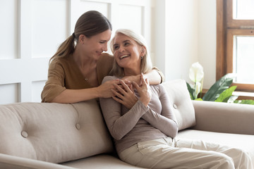 Loving adult daughter hugging older mother, standing behind couch at home, family enjoying tender...