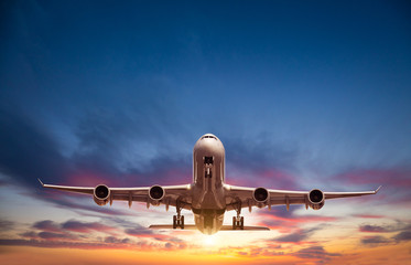 Passengers commercial airplane flying in sunset Fotobehang