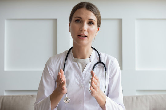 Head shot portrait woman doctor talking online with patient, making video call, looking at camera, young female wearing white uniform with stethoscope speaking, consulting and therapy concept