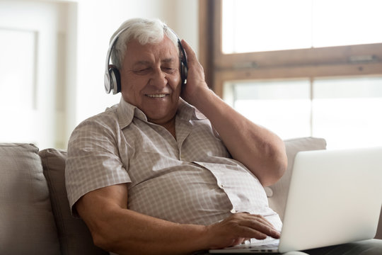 Smiling older man wearing wireless headphones enjoying popular music, using laptop, happy mature male touching headset, listening to favorite song, sitting on couch, elderly generation and technology