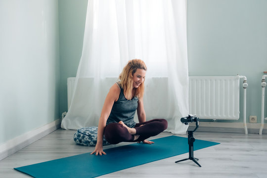 female yoga teacher connected from home blogging and vlogging broadcasting lesson via social media using smartphone on gimbal