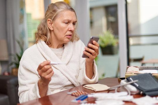 Sickness, seasonal virus problem concept. Senior woman being sick having flu at temperature on thermometer.