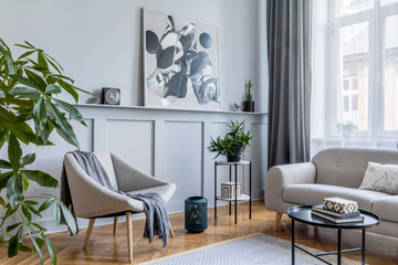 Stylish scandinavian home interior of living room with design gray sofa, armchair, marble stool,...