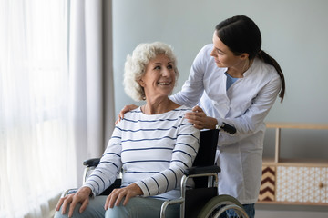 Fototapete - Young woman doctor give help support handicapped old lady patient sitting in wheelchair, female caregiver or nurse assist take care of smiling senior disabled grandma, elderly healthcare concept
