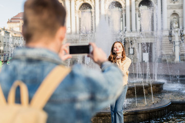 Selective focus of man taking picture with smartphone of woman blowing kiss near fountain in city