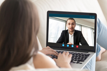 Young businesswoman talk chat with financial consultant on video call on laptop, female employee or client speak with male business partner use webcam computer conference, online consultation concept