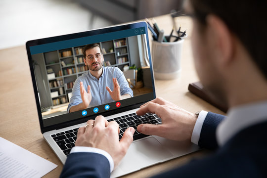 Back view of businessman talk with male business partner using video call on laptop discuss work project online, male client talk with colleague or coworker, speak on webcam conference on computer