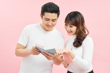 happy asian man and woman holding passports and air tickets while looking at camera isolated on pink