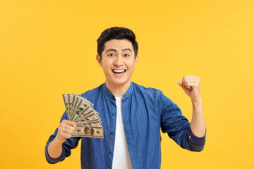 Portrait of excited amazed wondered astonished cheerful rejoicing manager showing many banknotes isolated on yellow background