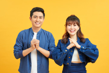Young couple posing in a yellow background clasping hands at camera in congratulations gesture.