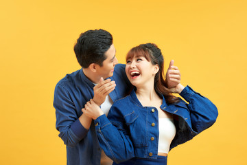 Couple playing hide and seek. Man standing behind his wife and closing her eyes, yellow background