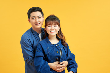 Happy casual couple embracing, posing to camera on yellow studio background
