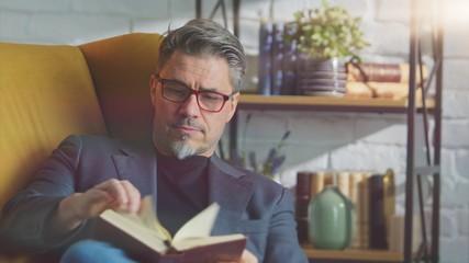 Older white man in glasses reading at home