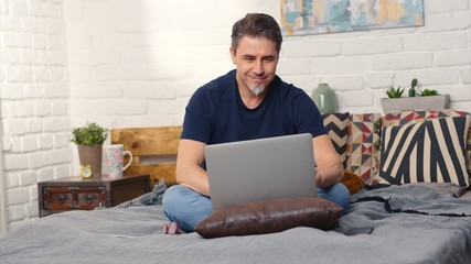 Stay at home and work in home office - Casual man sitting on bed working online from home with...