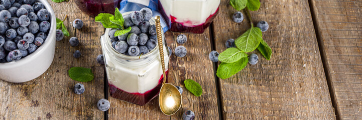 Sweet healthy yogurt with blueberry and blueberry jam in small portioned jars on wooden rustic table, copy space