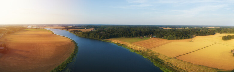 Rural aerial view of agriculture fields, meadows and beautiful river at sunset in Finland. View of fields before harvest at autumn. Fototapete