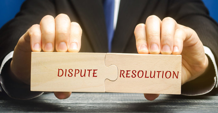 Man holds wooden puzzles with the words Dispute Resolution. Law and justice concept. Litigation, arbitration, mediation. ADR. Search for compromises. Lawyer services
