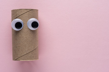 Completed toilet paper roll with googly eyes on pink background. Minimal Coronavirus outbreak. Panic concept.