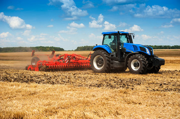 blue new tractor pulls a red harrow raises dust at the field, soil preparation