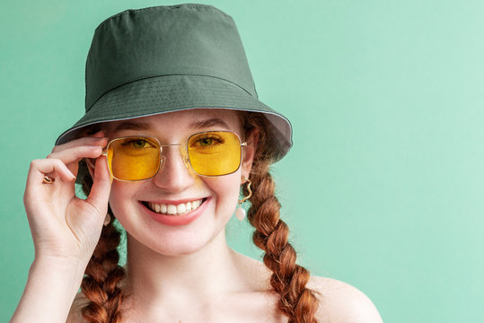 Happy smiling fashionable woman wearing yellow square sunglasses, trendy green bucket hat. Close up portrait. Copy, empty space for text