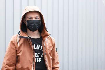 Stylish young man in black face mask on grey background. Coronavirus quarantine situation. Street style during the epidemic. Protection medical respirator as pandemic clothing item. Pandemic lifestyle Wall mural