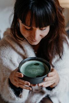 Portrait einer dunkelhaarigen Frau Zuhause die einen  Matcha Tee trinkt