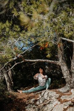 Frau die draußen am Meer auf Mallorca Yoga praktiziert