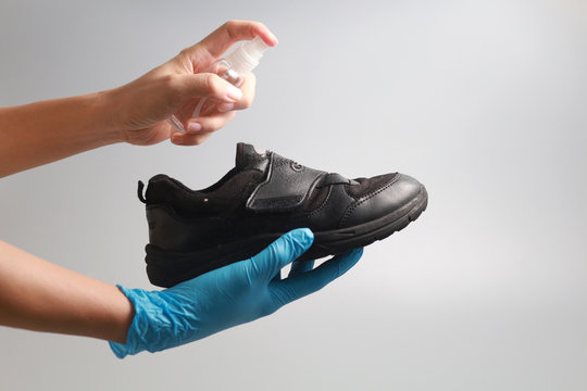Close up hand cleaning shoes with alcohol spray against grey background. Concept of personal belongings for disease prevention from bacteria and virus.