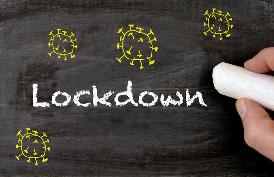 Blackboard with virus drawings and hand writing lockdown