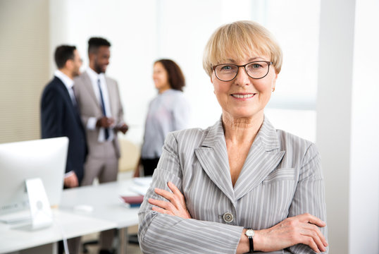 Portrait of happy mature business woman in an office with colleagues on the background