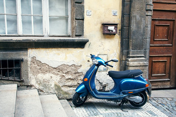 Fotorolgordijn Scooter Blue vintage scooter parked in a city.