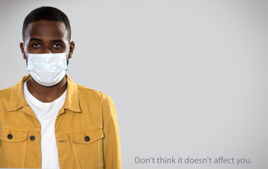 Сoronavirus. Serious africanamerican man in medical mask on a gray background with space for text.