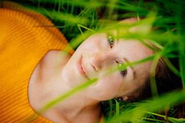 Young woman lies on her back in the green grass