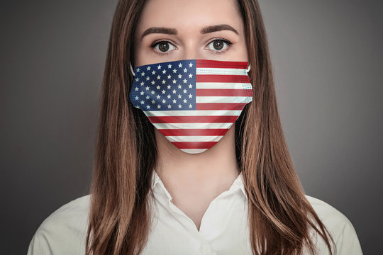 Portrait of scared girl wearing a medical respiratory mask with print of the USA flag, coronovirus epidemic, quarantine, pandemic concept